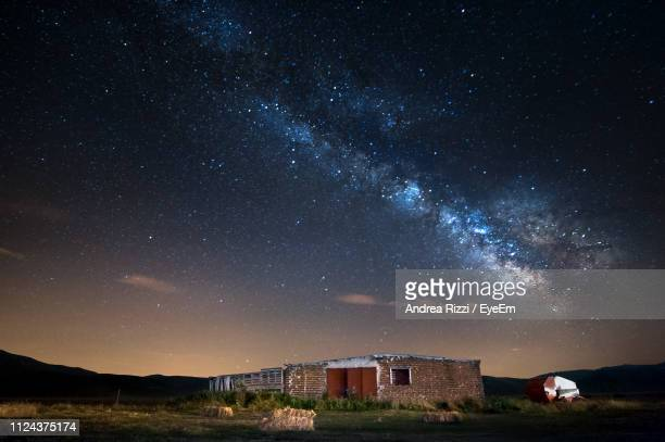 buildings on field against sky at night - andrea rizzi stock pictures, royalty-free photos & images