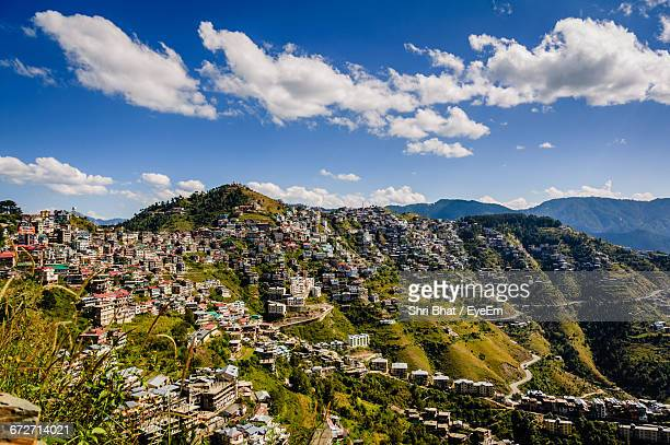 buildings on mountain against cloudy blue sky during sunny day - shimla stock pictures, royalty-free photos & images