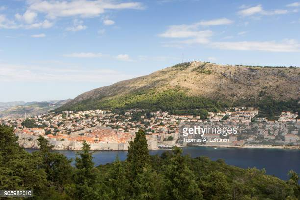 Buildings on the hillside and Mount Srd in Dubrovnik, Croatia, viewed from the lush Lokrum Island on a sunny day. Copy space.