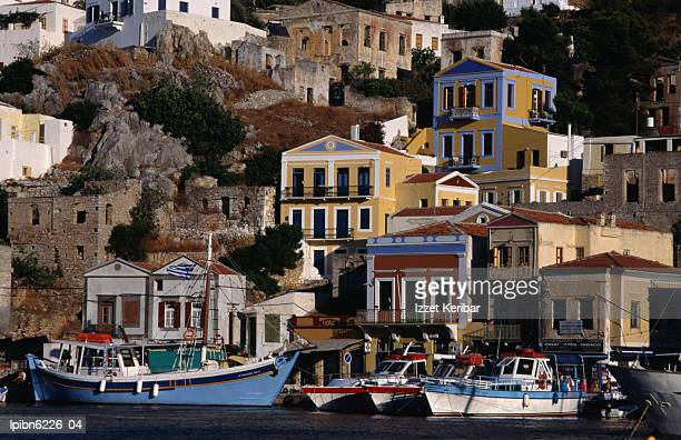 buildings overlooking the harbour., symi island, southern aegean, greece, europe - symi foto e immagini stock