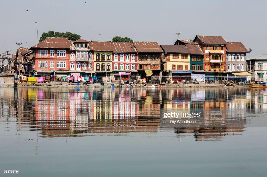 Buildings reflected in still river : Foto stock