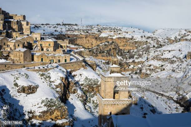 Buildings seen covered by snow after a long snowfall when the sun shines on the snowcovered rocks of matera making a beautiful postcard of the...