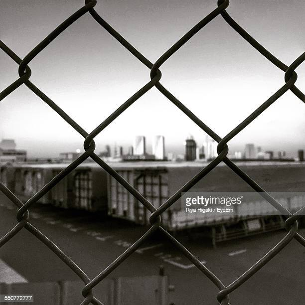 Buildings Seen Through Chainlink Fence Against Clear Sky