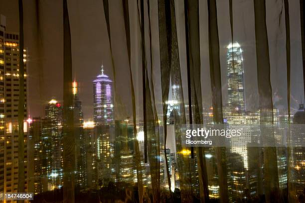 Buildings shot through curtains stand illuminated at night in the Central district in Hong Kong China on Tuesday Oct 8 2013 Property market...