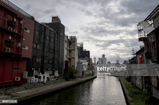 Buildings stand along a river in Wakayama Japan on Monday Sept 11 2017 Wakayama is one of Japan's least populated and fastestaging prefectures...