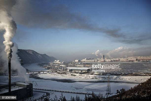 Buildings stand as water vapor and smoke rise from a Tonghua Iron Steel Group Co plant in the distance in the Erdaojiang district in Tonghua Jilin...