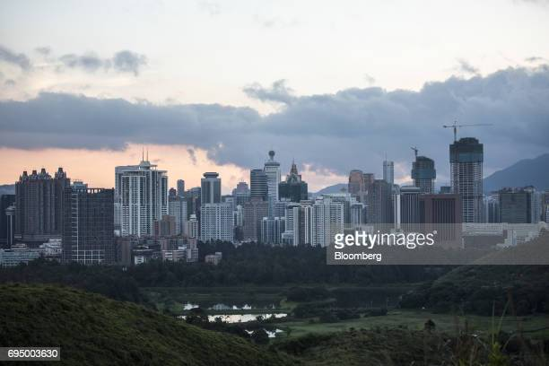 Buildings stand at dawn on the Shenzhen side of the border beyond farmland in the Ma Tso Lung district of Hong Kong China on Thursday June 8 2017...