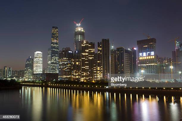 Buildings stand illuminated at dusk in the Zhujiang New Town district of Guangzhou China on Friday Nov 29 2013 China's government may set its 2014...