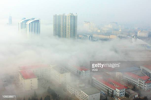 Buildings stand in fog shrouded Qinhuangdao City on February 22 2011 in Hebei Province of China China's National Meteorological Center has issued a...