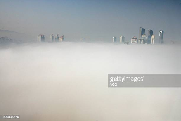 Buildings stand in fog shrouded Yantai City on February 21 2011 in Shandong Province of China China's National Meteorological Center has issued a...