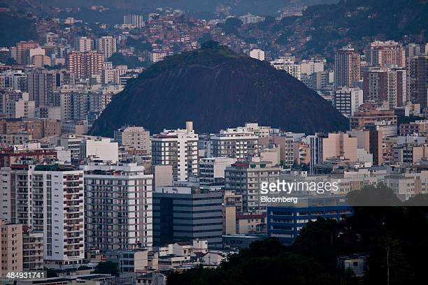 Buildings stand in the Tijuca neighborhood foreground next to a favela at rear in Rio de Janeiro Brazil on Saturday April 12 2014 Brazil's economic...
