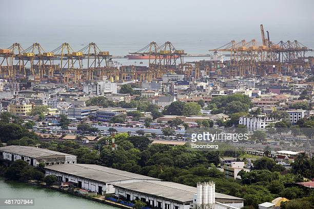 Buildings stand near Beira Lake as gantry cranes at the Port of Colombo stand in the background in Colombo Sri Lanka on July 20 2015 Sri Lanka will...
