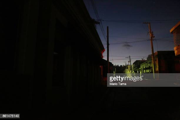 Buildings stand on a mostly darkened street on October 14 2017 in Yauco Puerto Rico Puerto Rico is suffering shortages of food and water in many...