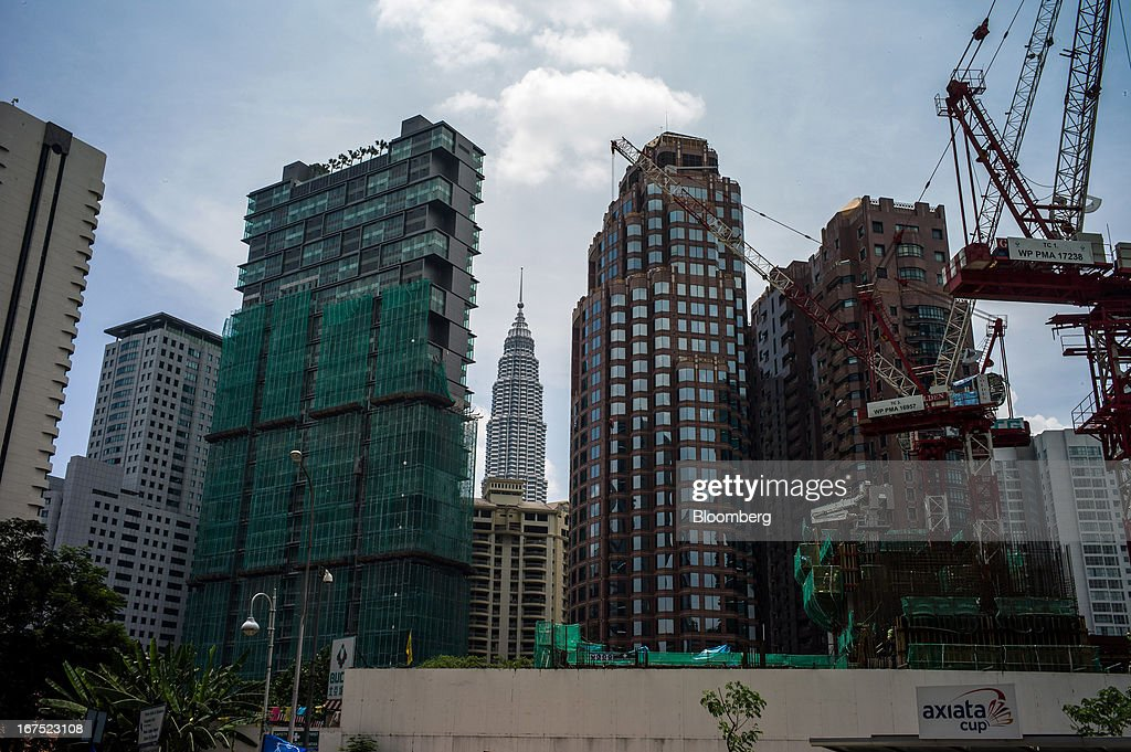 Buildings stand under construction as one the Petronas Twin Towers is seen in the background, center, in Kuala Lumpur, Malaysia, on Thursday, April 25, 2013. Malaysians will go to the polls on May 5. Prime Minister Najib Razak's National Front coalition is seeking to extend its 55 years of unbroken rule in the face of a resurgent opposition led by Anwar Ibrahim. Photographer: Sanjit Das/Bloomberg via Getty Images