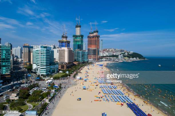 Buildings stand under construction beyond bathers on the beach and in the sea in this aerial photograph taken above Haeundae beach in Busan South...