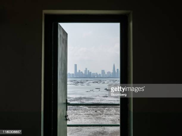 Buildings standing in Shenzhen are seen through the doorway of the former Lau Fau Shan Police Station in the Lau Fau Shan district of Hong Kong,...