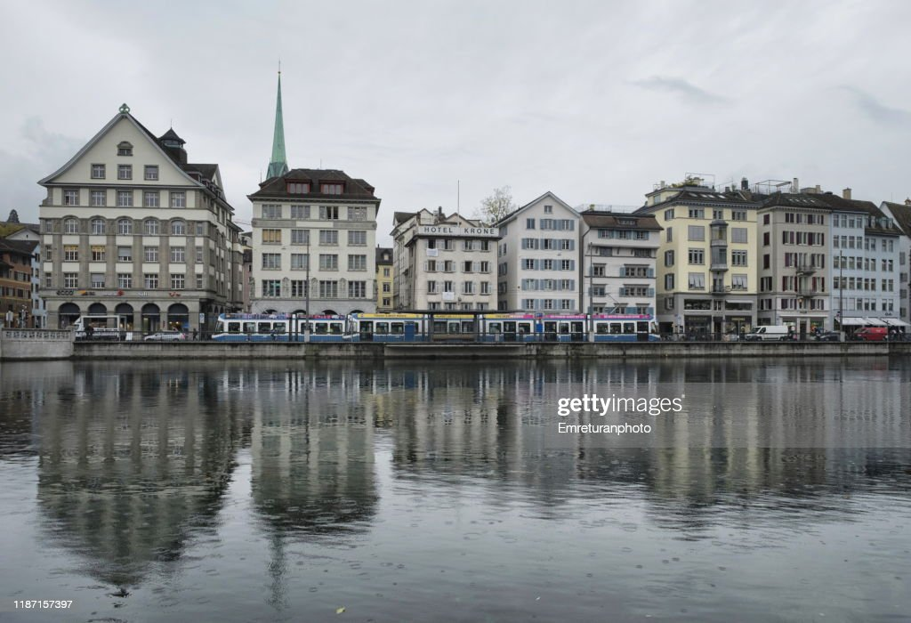 Buildings ,tram and reflections on left side of Limmat river ,Zurich. : Stock Photo