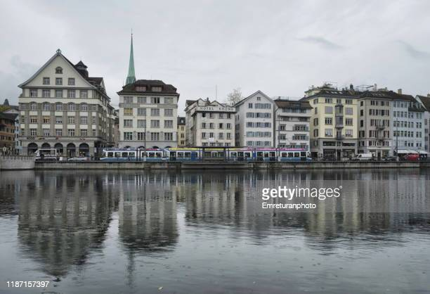 buildings ,tram and reflections on left side of limmat river ,zurich. - emreturanphoto stock pictures, royalty-free photos & images