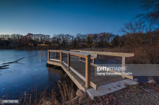 built structure by calm lake against blue sky - kalamazoo stock pictures, royalty-free photos & images