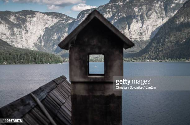 built structure by lake against mountains - christian soldatke stock pictures, royalty-free photos & images