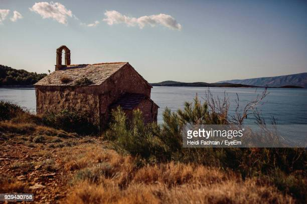 built structure by lake against sky - hvar stock photos and pictures