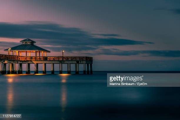 built structure by sea against sky during sunset - fort myers beach stock pictures, royalty-free photos & images