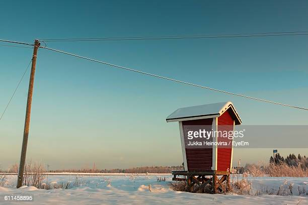 built structure by telephone pole on snowy field against clear sky - heinovirta stock pictures, royalty-free photos & images