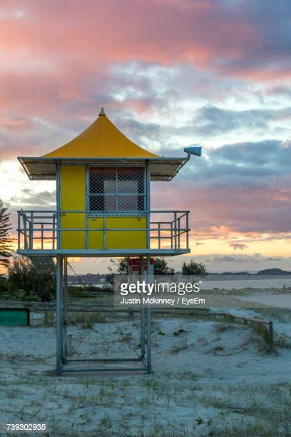 Built Structure On Beach Against Sky During Sunset