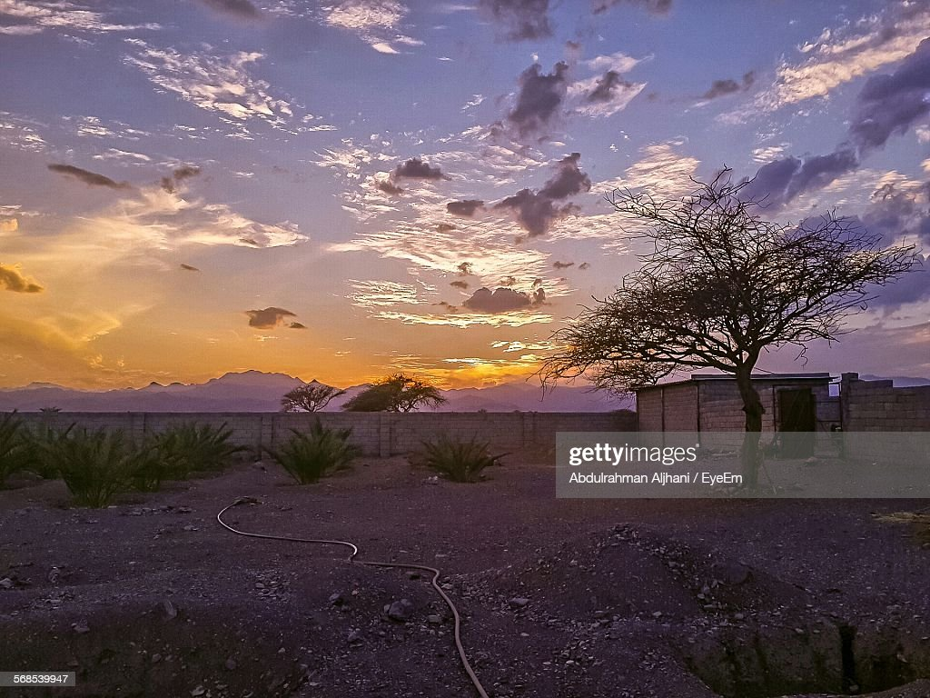 Built Structure On Field Against Sky At Sunset : Stock Photo