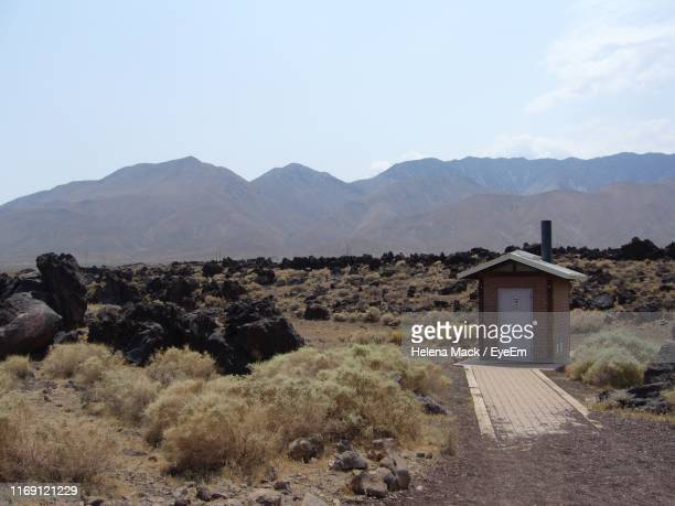 built structure on field by mountains against sky - mack stock pictures, royalty-free photos & images