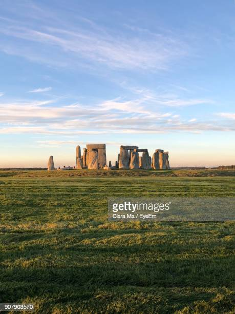 built structure on landscape against sky - stonehenge stock photos and pictures