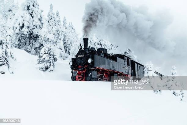 built structure on snow covered land against sky - steam train stock pictures, royalty-free photos & images