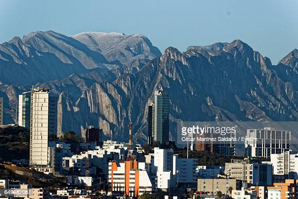 built structures against rocky mountain range - monterrey fotografías e imágenes de stock