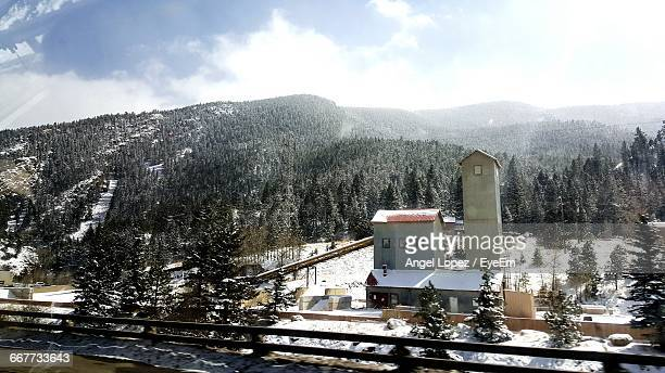 built structures on snow covered landscape against trees - lopez stock pictures, royalty-free photos & images