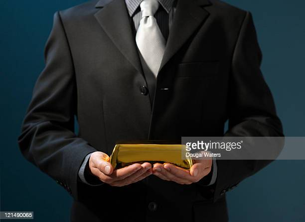 Buiness man holding gold bar.