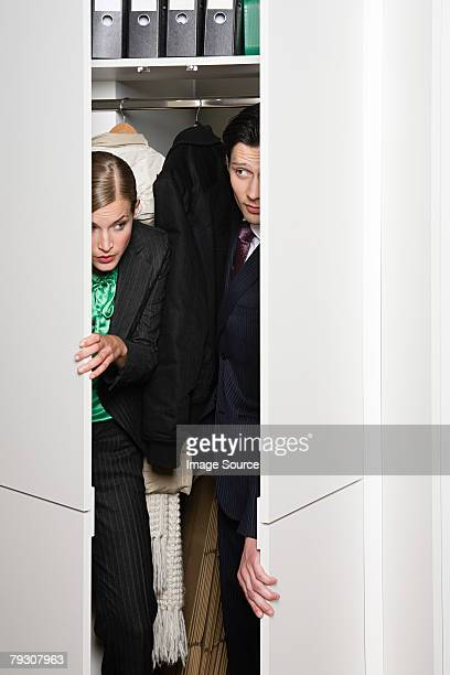 Buisnesswoman and man sneaking out of closet
