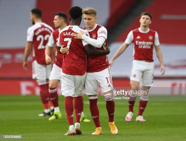 Bukayo Saka hugs Martin Odegaard of Arsenal before the Premier League match between Arsenal and Manchester City at Emirates Stadium on February 21,...