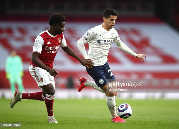 Bukayo Saka of Arsenal battles for possession with Joao Cancelo of Manchester City during the Premier League match between Arsenal and Manchester...