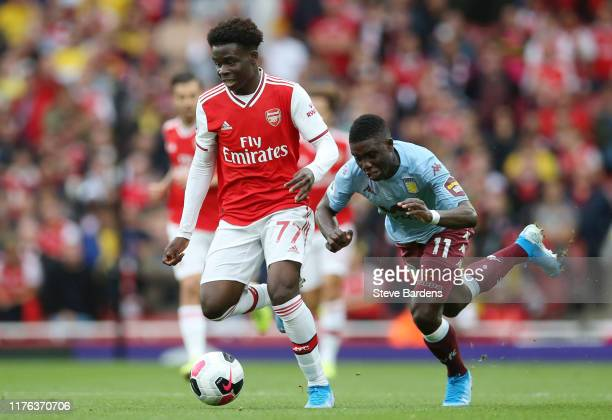 Bukayo Saka of Arsenal breaks away from Aston Villa defenders during the Premier League match between Arsenal FC and Aston Villa at Emirates Stadium...