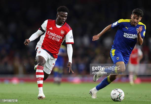 Bukayo Saka of Arsenal breaks away from Will Nightingale of AFC Wimbledon during the Carabao Cup Third Round match between Arsenal and AFC Wimbledon...
