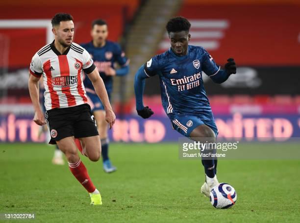 Bukayo Saka of Arsenal breaks past George Baldock of Sheffield United during the Premier League match between Sheffield United and Arsenal at Bramall...