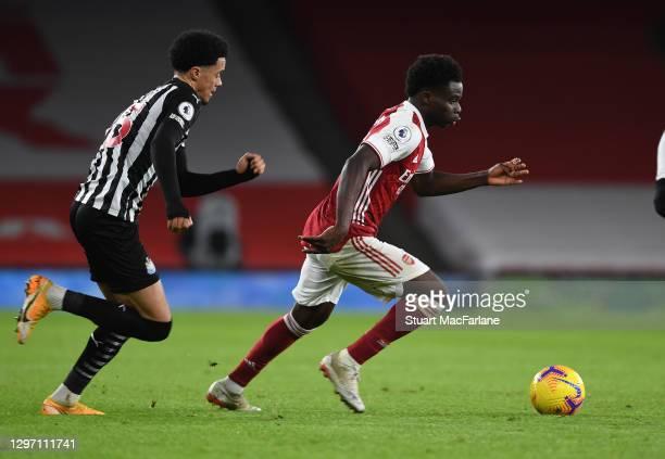 Bukayo Saka of Arsenal breaks past Jamal Lewis of Newcastle United during the Premier League match between Arsenal and Newcastle United at Emirates...