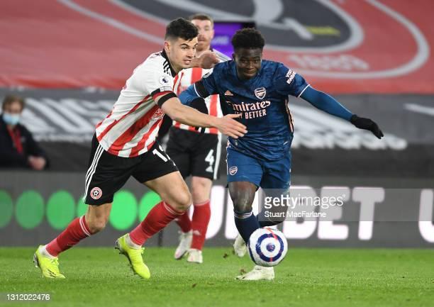 Bukayo Saka of Arsenal breaks past John Egan of Sheffield United during the Premier League match between Sheffield United and Arsenal at Bramall Lane...