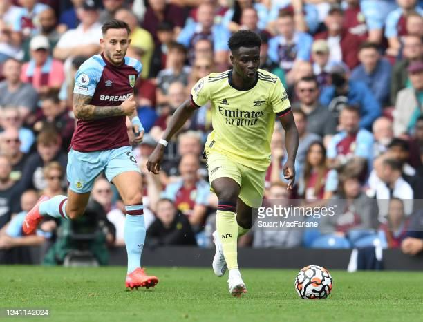 Bukayo Saka of Arsenal breaks past Josh Brownhill of Burnley during the Premier League match between Burnley and Arsenal at Turf Moor on September...