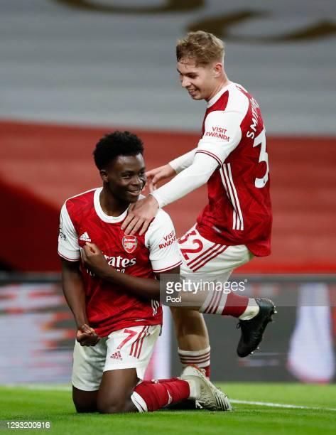 Bukayo Saka of Arsenal celebrates with teammates Emile Smith Rowe after scoring his team's third goal during the Premier League match between Arsenal...