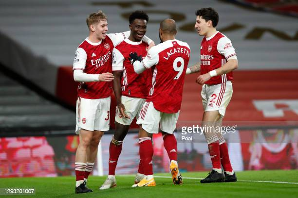 Bukayo Saka of Arsenal celebrates with teammates Emile Smith Rowe, Alexandre Lacazette, and Hector Bellerin after scoring his team's third goal...