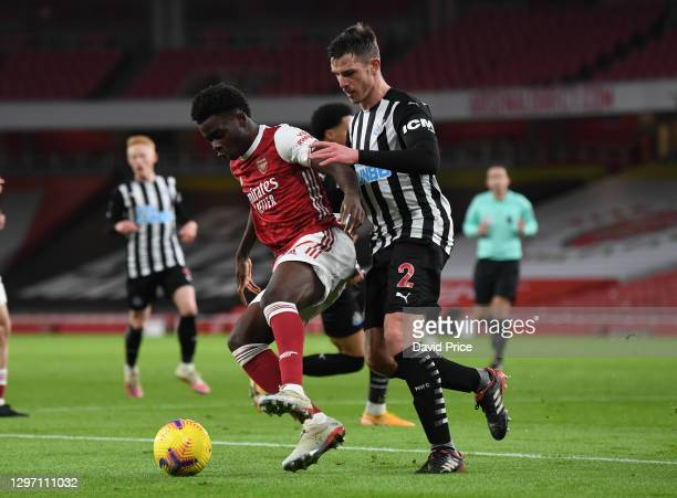 Bukayo Saka of Arsenal controls the ball under pressure from Ciaran Clark of Newcastle during the Premier League match between Arsenal and Newcastle...