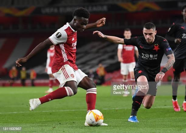 Bukayo Saka of Arsenal crosses the ball under pressure from Nicolae Stanciu of Slavia during the UEFA Europa League Quarter Final First Leg match...