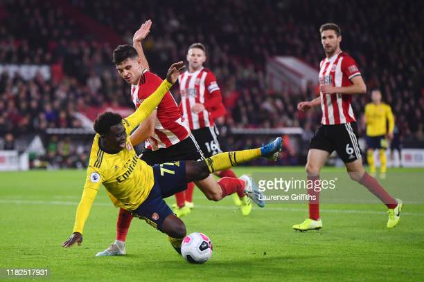 Bukayo Saka of Arsenal goes down after he battles for possession with John Egan of Sheffield United during the Premier League match between Sheffield...
