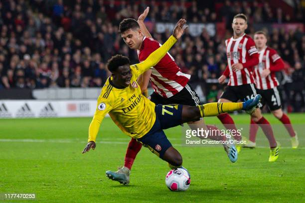 Bukayo Saka of Arsenal goes down under challenge by John Egan of Sheffield United but is deemed to have dived during the Premier League match between...